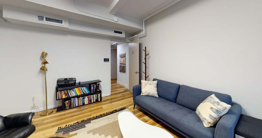 psychotherapy office in NYC with wood floors and blue couch